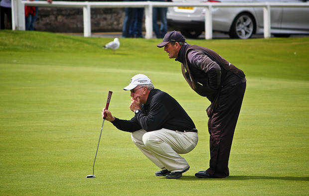 Two golfers examining a shot