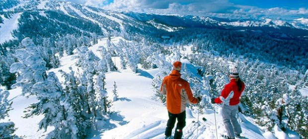 Two skiers atop a snowy slope